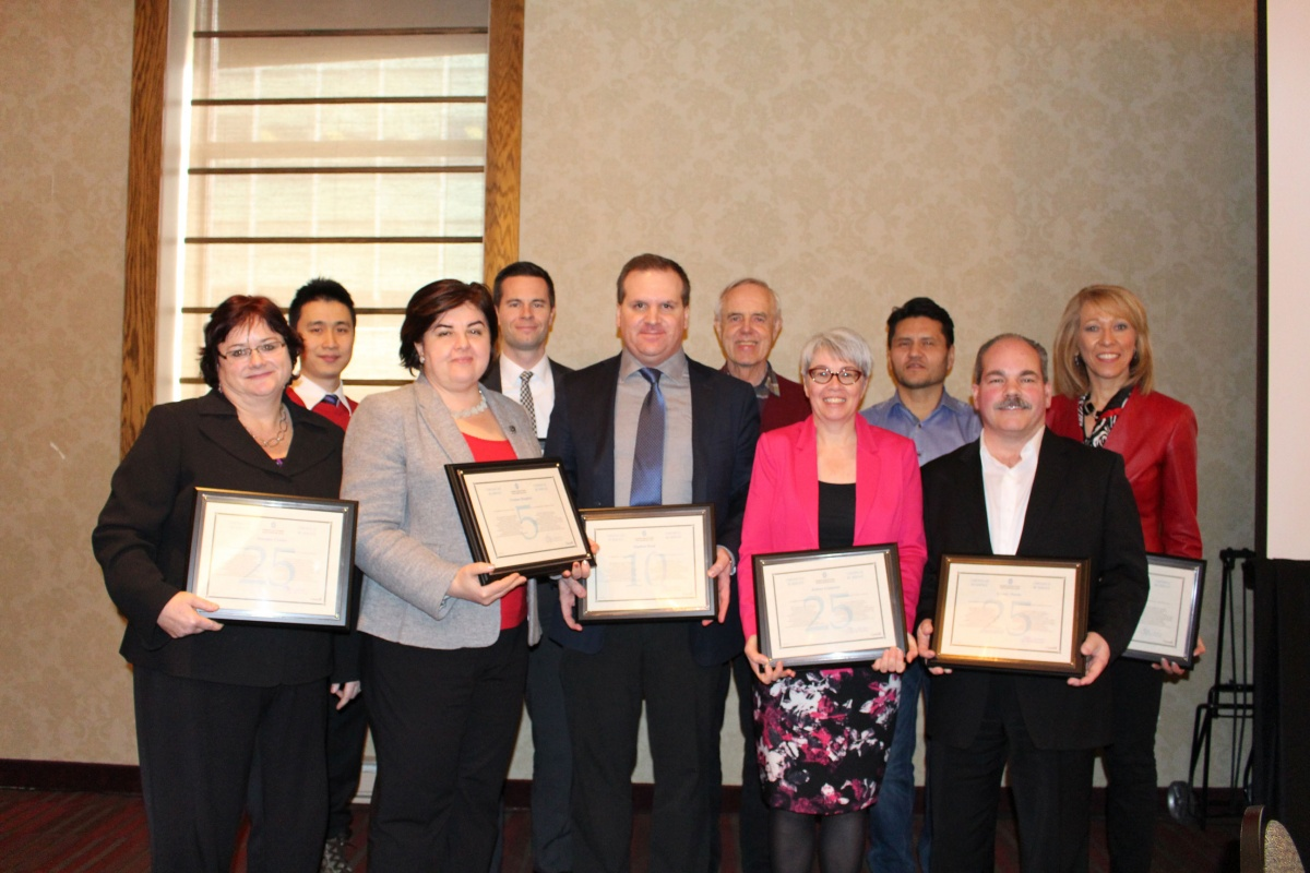 Group of people with their framed service awards.