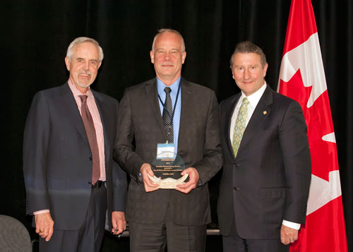 Stephen Cross receives the dedicated service award, accompanied by John Walter and Sam Shaw.