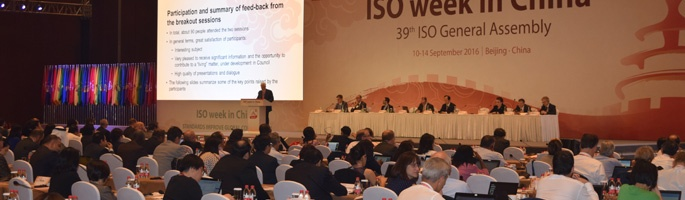 John Walter speaking in front of large audience at ISO General Assembly